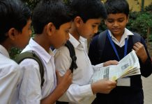 School children in Murshidabad share a newspaper.